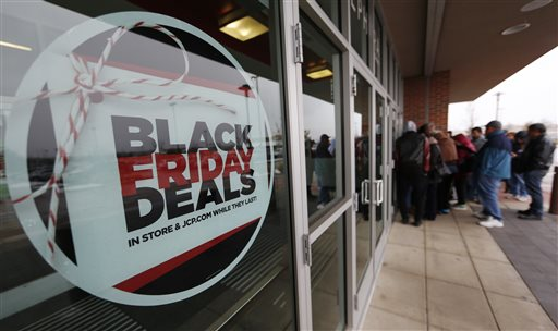A sign promoting Black Friday specials is displayed in the window of a J.C. Penny store as shoppers queue up at the door for a 3 p.m. opening, Thursday, Nov. 26, 2015, in northeast Denver. (AP Photo/David Zalubowski)