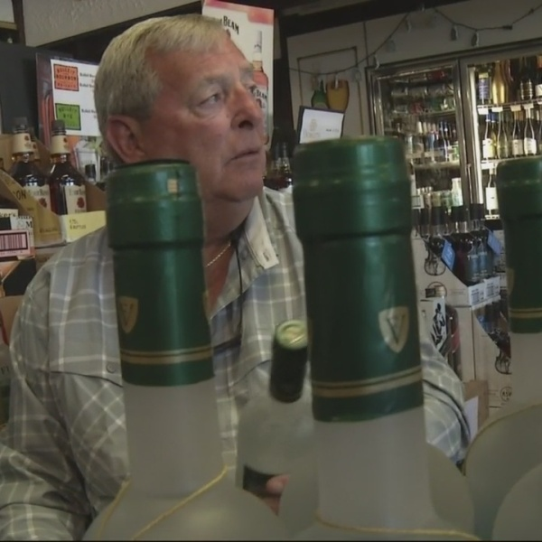 Masters champion Fuzzy Zoeller autographing bottles of his vodka